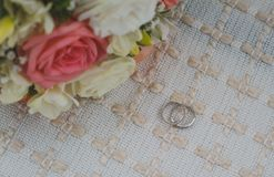 White gold wedding rings lie on a beige rug, a bridal bouquet royalty free stock photo