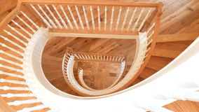 White and Golden Brown Wooden Spiral Staircase Looking Down stock photos