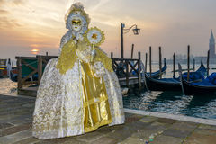 White and golden costumed masked woman. In front of gondolas in Venice at sunrise Stock Images