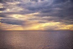 White and golden sun`s rays make their way through the clouds. White and golden sun`s rays make their way through the storm clouds over the sea Royalty Free Stock Photography