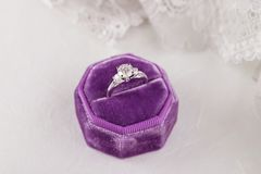 White golden wedding ring with diamonds in purple vintage velvet. Ring box on gray lace background. Silver engagement ring. Nuptials lifestyle Royalty Free Stock Images