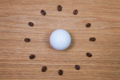White golf ball and clock of coffee beans Royalty Free Stock Photo