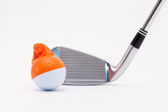 White golf ball with funny cap and golf club on the white backgr Stock Photography