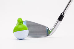 White golf ball with funny cap and golf club on the white backgr Royalty Free Stock Photography