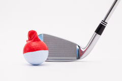 White golf ball with funny cap and golf club on the white backgr Stock Images