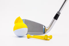 White golf ball with funny cap and golf club on the white backgr Royalty Free Stock Photos