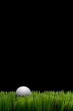 A white golf ball in green grass. Vertical image of a white golf ball in green grass on a black background with space for copy Stock Photo