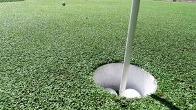 White golf ball hitting flag stick and falling into hole on putting green