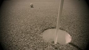 White golf ball hitting flag stick and falling into hole on putting green - Hole in one Stock Image