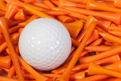 White golf ball lying between wooden tees. White golf ball lying between orange wooden golf tees Royalty Free Stock Photos