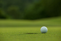 White golf ball near hole on fairway with the green background i Royalty Free Stock Images