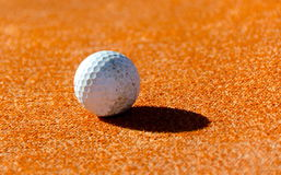 White golf ball on orange field. White golf ball throwing a long shade on orange textured carpet Stock Images