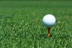 White golf ball on a orange tee. A White golf ball on a orange tee Royalty Free Stock Photos