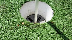 White golf ball rolling in the cup on artificial putting green