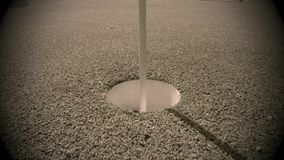 White golf ball rolling in the cup on artificial putting green stock footage