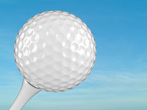 White golf ball on tee. With blue sky on the background Stock Photos