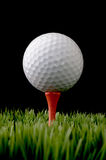 A white golf ball on a tee on black Royalty Free Stock Image