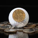 White golf ball and U.S. dollar coins Stock Image