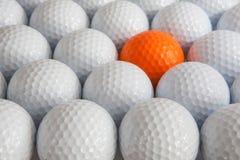 White golf balls. And one orange balls in the box Stock Image