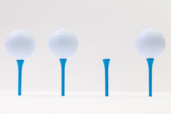 White golf balls and blue tees on the white table Royalty Free Stock Images