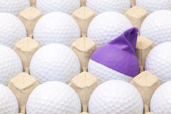 White golf balls in the box for eggs. Golf ball with funny cap. Royalty Free Stock Photos