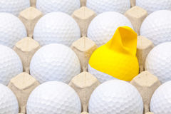 White golf balls in the box for eggs. Golf ball with funny cap. Stock Image