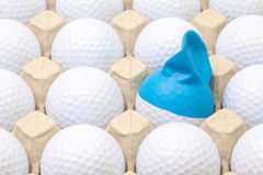 White golf balls in the box for eggs. Golf ball with funny cap. Royalty Free Stock Photo