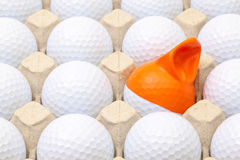 White golf balls in the box for eggs. Golf ball with funny cap. Royalty Free Stock Photography