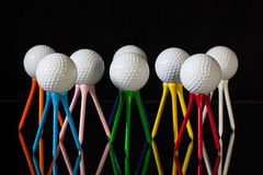 White golf balls and different colored tees Royalty Free Stock Image