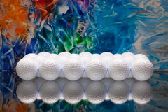 White golf balls on a glass desk Royalty Free Stock Photography