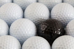 White golf balls and one black ball Stock Images