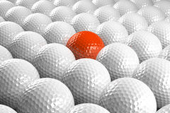 White Golf balls & one orange in the middle Stock Photography