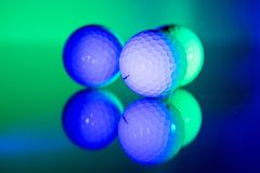 White golf balls on a plate of glass creating a mirror view, illuminated in bright green and blue color stock photo