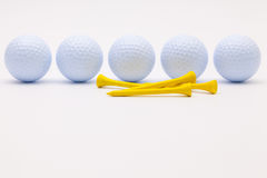 White golf balls and wooden tees on the white background. royalty free stock photos
