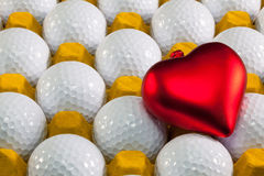 White golf balls in the yellow box and love symbol. White golf balls in the yellow box and red heart Royalty Free Stock Images