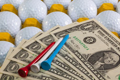 White golf balls in the yellow box and US money Royalty Free Stock Images