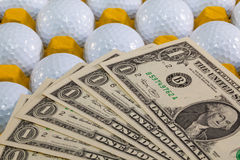 White golf balls in the yellow box and US money Stock Photos