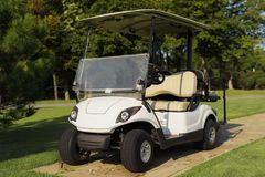White golf cart on the stone path in the golf club. A stylish white golf club stands on a stone path in a golf club, against a background of trees Royalty Free Stock Photography