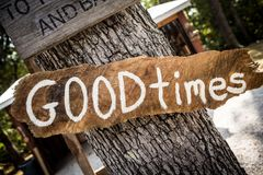 Good Times sign on wooden board. White Good Times hand painted sign on rough wooden board nailed to tree trunk in park or camping place royalty free stock image