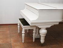 White grand piano. And bench in a room royalty free stock photo