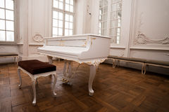 White grand piano. Standing in elegant white interior of palace hall royalty free stock photo