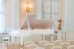 White grand piano on concert hall. With rows of chairs Royalty Free Stock Photography
