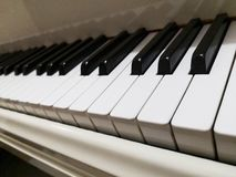 White grand piano. no brand shown as copyright issue. the focus on the front tuts. White grand piano brand shown copyright issue focus front tuts keys royalty free stock photography