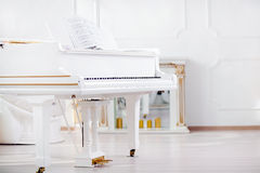 White grand piano standing in elegant interior of palace hall. White grand piano standing in elegant white interior royalty free stock images