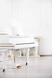 White grand piano standing in elegant interior of  palace hall. Grand piano standing in elegant white interior Royalty Free Stock Photo