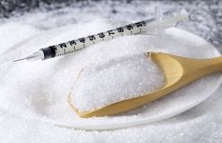 White granulated sugar pile in white dish with syringe and woode Royalty Free Stock Images