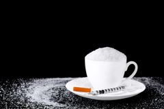 White granulated sugar pouring growing into cup coffee with syri. Nge on black background Royalty Free Stock Photo