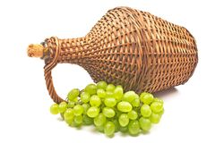White grape with old wicker wrapped glass bottle isolated  on white Royalty Free Stock Photography