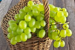 White grape with on old wicker wrapped glass bottle on wooden ta Royalty Free Stock Photos