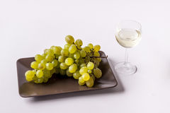 White grapes with a glass of white wine -white bac. White grapes with a glass of white wine on white background Royalty Free Stock Image
